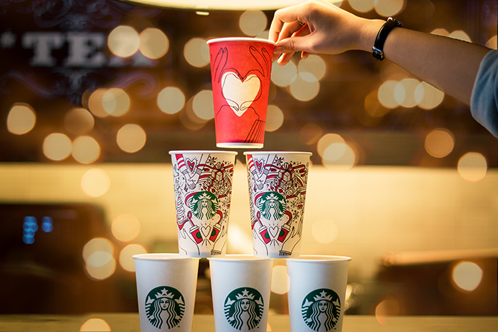 A pyramid of takeaway coffee cups with a beautiful Christmas bokeh background
