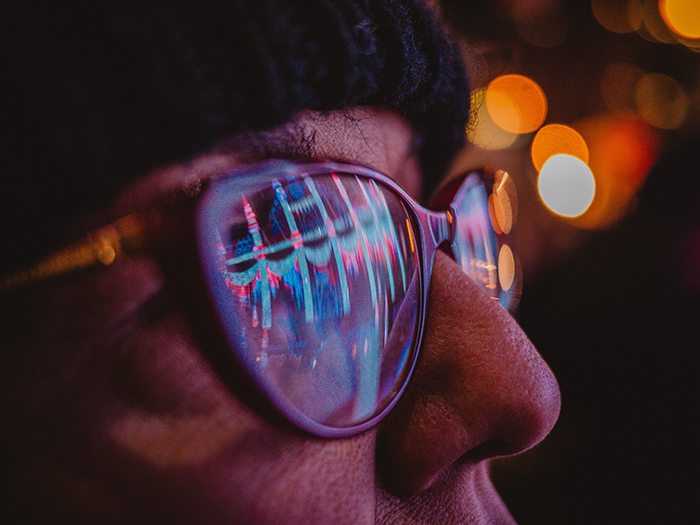 Christmas lights reflected in a persons glasses