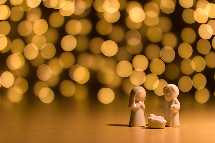 Beautiful Christmas bokeh lights in the background of small nativity figures