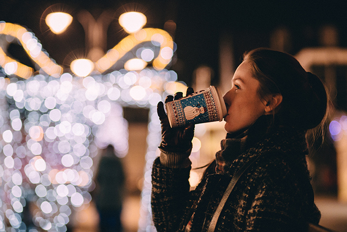 A portrait of a girl drinking hot chocolate, with a beautiful Christmas bokeh background
