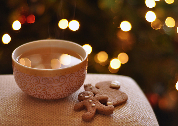 A bowl of hot drink beside gingerbread with a beautiful Christmas bokeh background