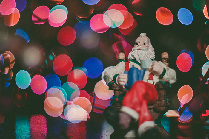 A santa figurine with Christmas bokeh lights background