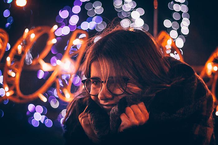 Potrait feminino à noite com fundo de luzes bokeh