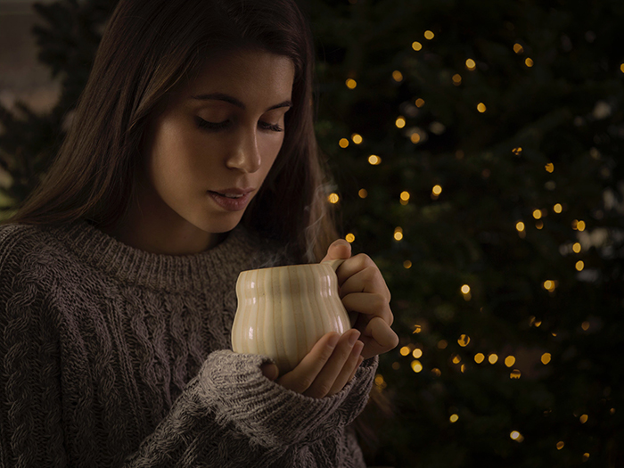A female portrait in front of a Christmas tree with bokeh lights background