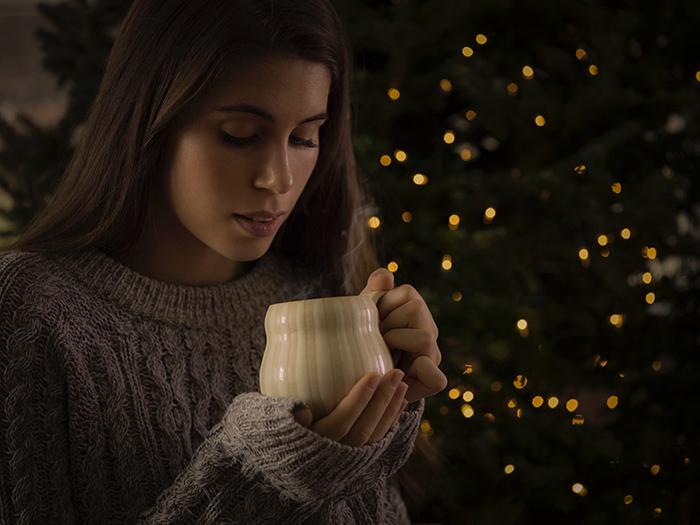 Um retrato feminino em frente a uma árvore de Natal com luzes bokeh de fundo