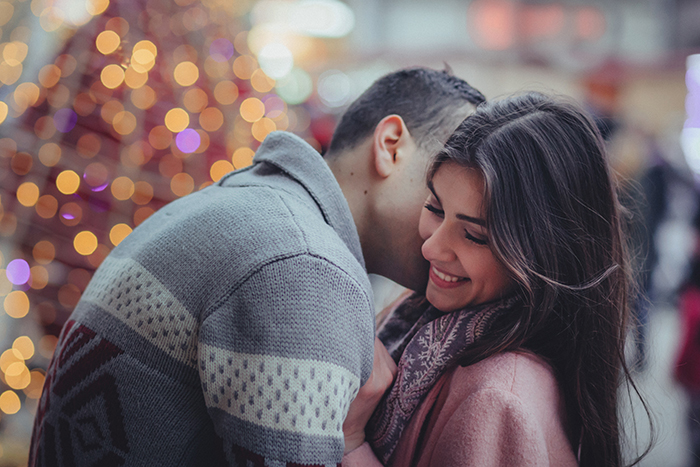 A couple embrace in front of a Christmas tree with bokeh lights background