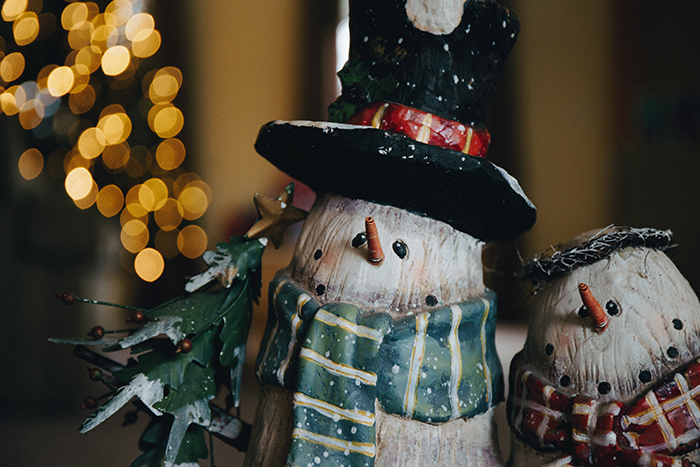 A pair of snowman ornaments with bokeh lights background