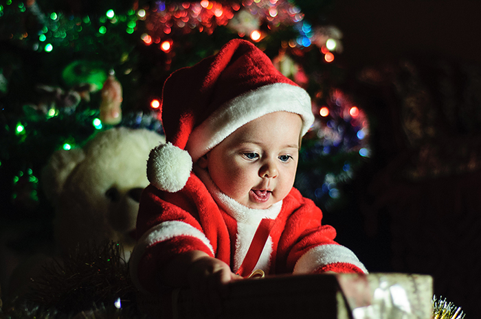 A cute Christmas portrait of a baby in a santa suit
