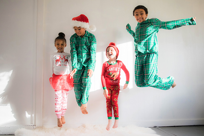 A cute Christmas photography shoot of four kids jumping excitedly on a bed