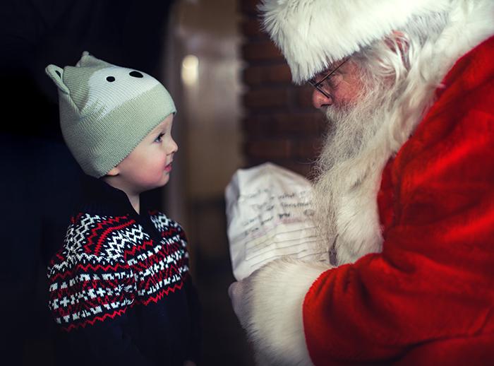 An indoor Christmas portrait of a little boy meeting a Santa Claus