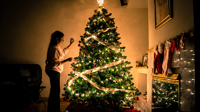 Atmospheric Christmas photography of a girl dressing a tree