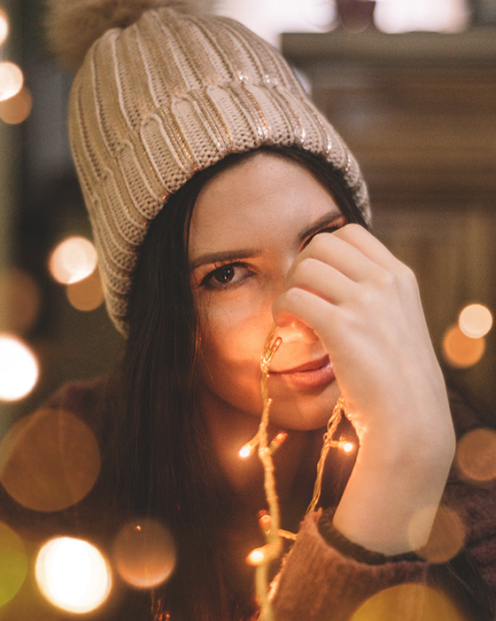 A girl posing indoors with christmas lights and beautiful bokeh effects