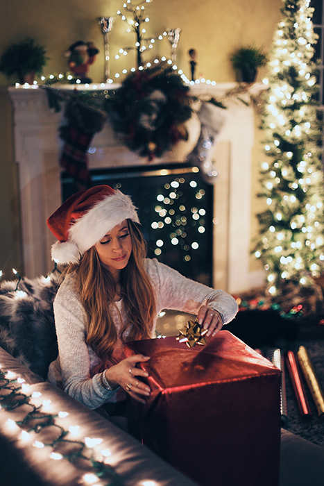 Atmospheric Christmas photography of a girl opening a present