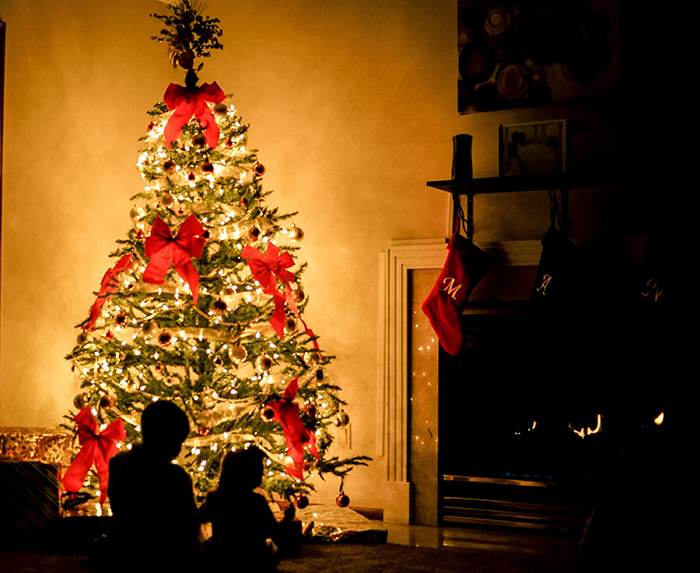 Silhouettes of children in front of the Christmas tree