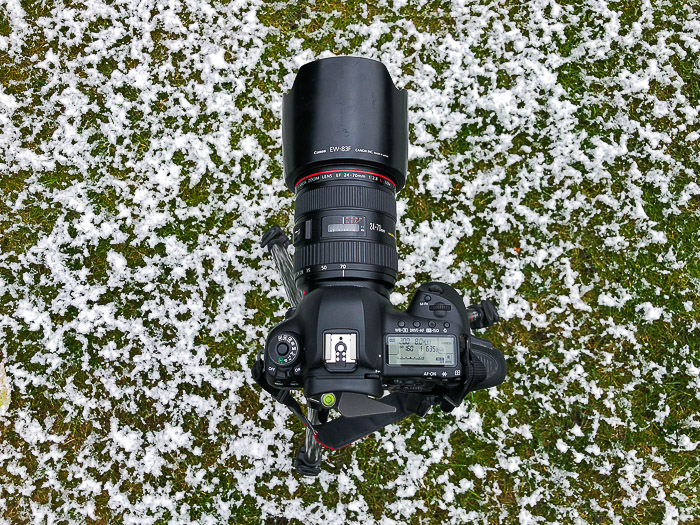 A DSLR with zoom lens resting on snowy grass - stock photography equipment