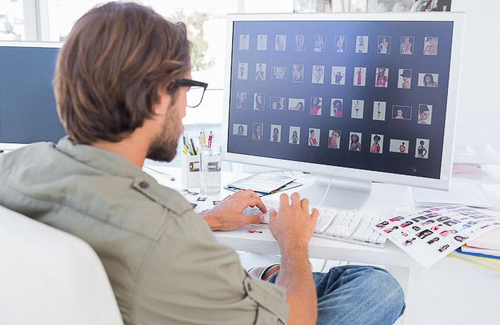 A photographer editing stock photos on a computer