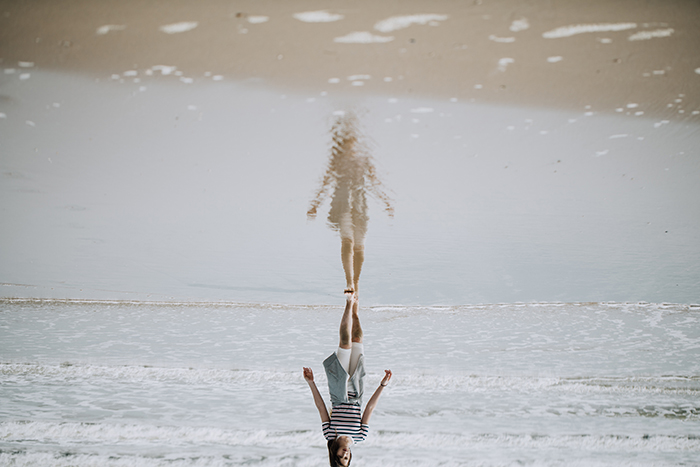 A fine art photo of a girl on a beach at an upside down angle -