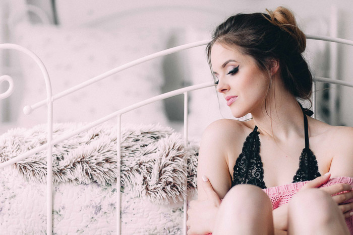 Bright and airy glamour photography portrait of a beautiful female model posing by a bed
