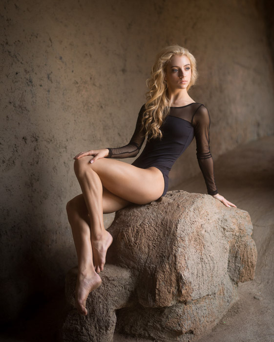 A female model poses on a rock - tips for taking glamour shots