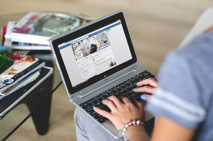 A photo of a person resizing images on a laptop for facebook