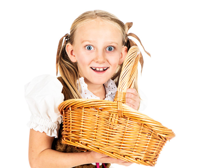 A high key photo of a little girl holding a wicker basket
