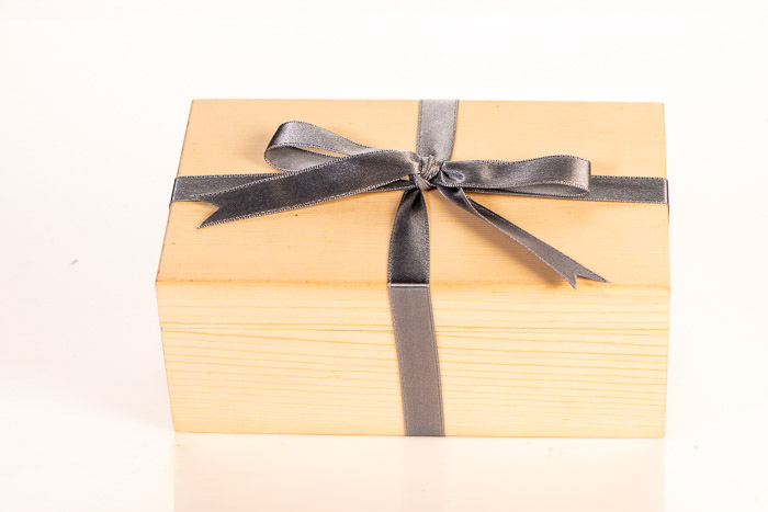 A wooden box wrapped with a grey bow against a white background