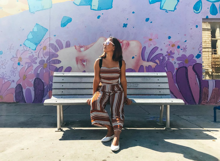 A female model posing on a bench taken with an iphone photo timer