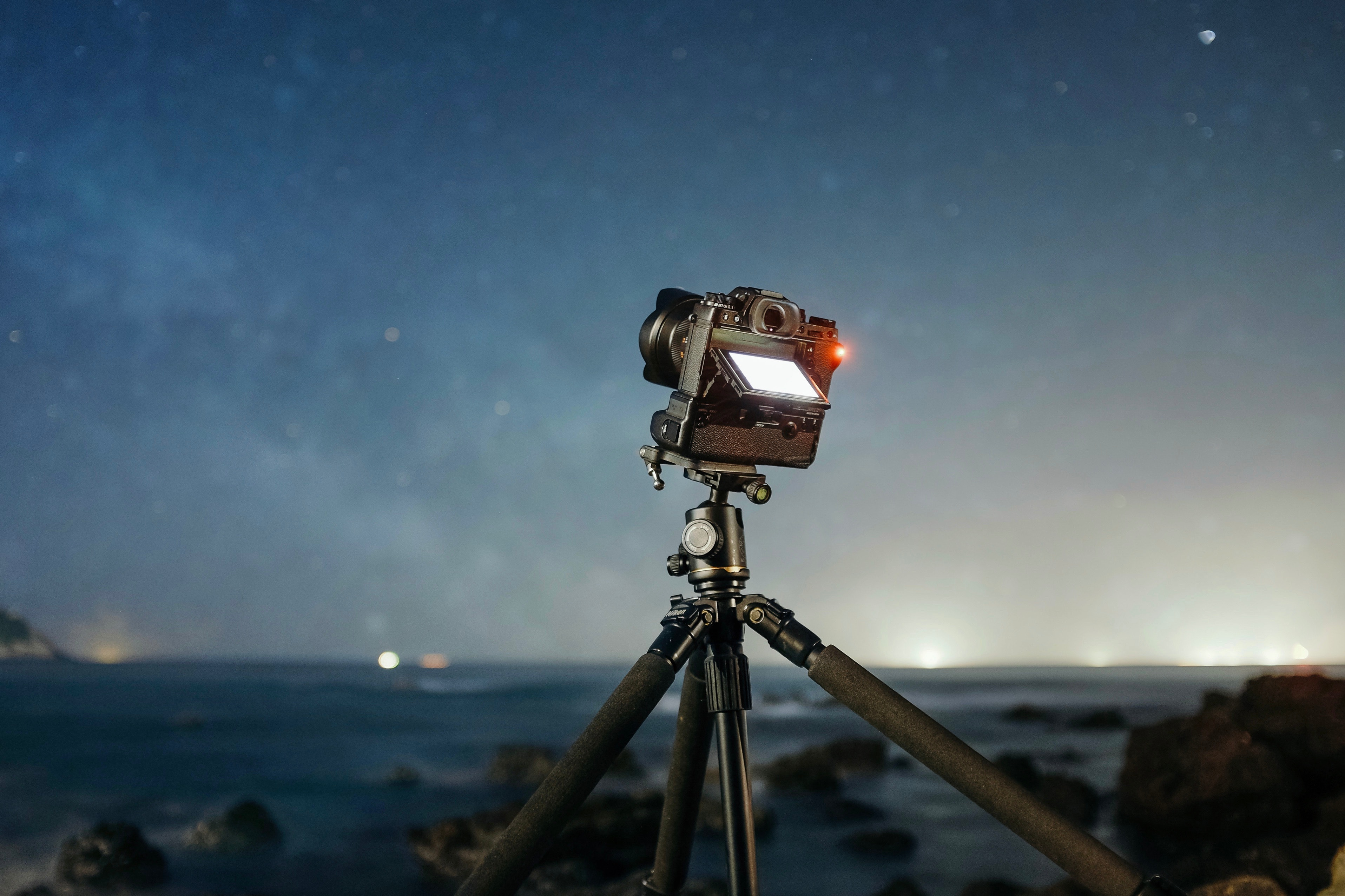 A DSLR camera set up on a tripod outdoors at night