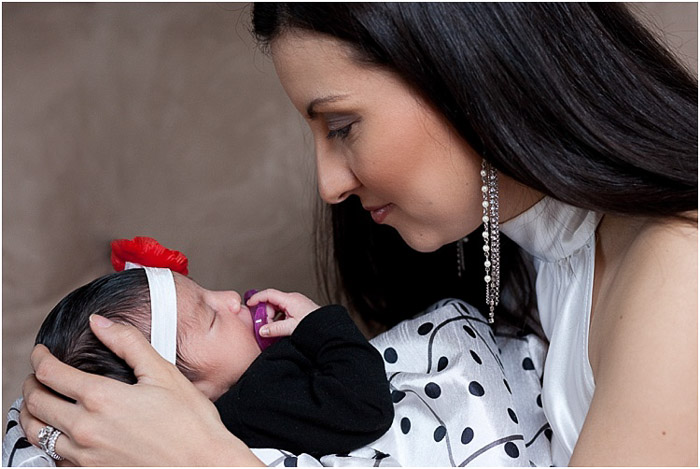 A mother posing with newborn baby for a session at a newborn photography business