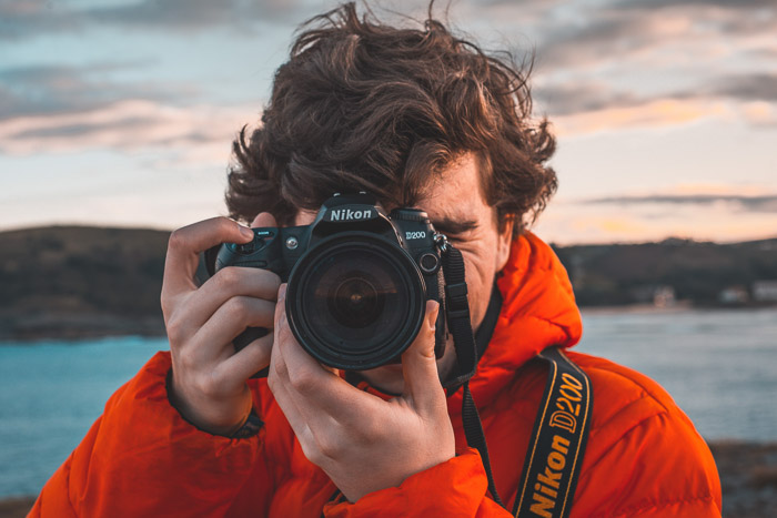 A man in orange jacket holding a Nikon DSLR camera - photography marketing ideas