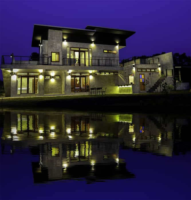 Stricking architectural shot of a house at dusk with a cool Photoshop reflection in the water below