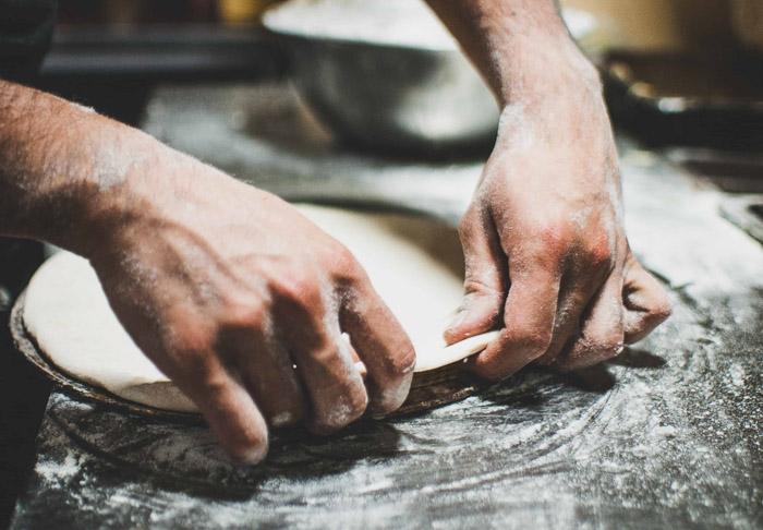 A close up of a person preparing pizza dough