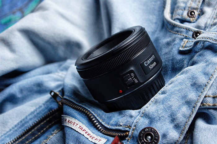 A Canon 50mm prime lens for pet photography resting on a denim jacket