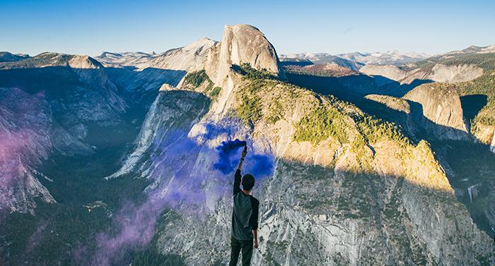 Impressive portrait of a man waving blue smoke grenades in a mountainous landscape