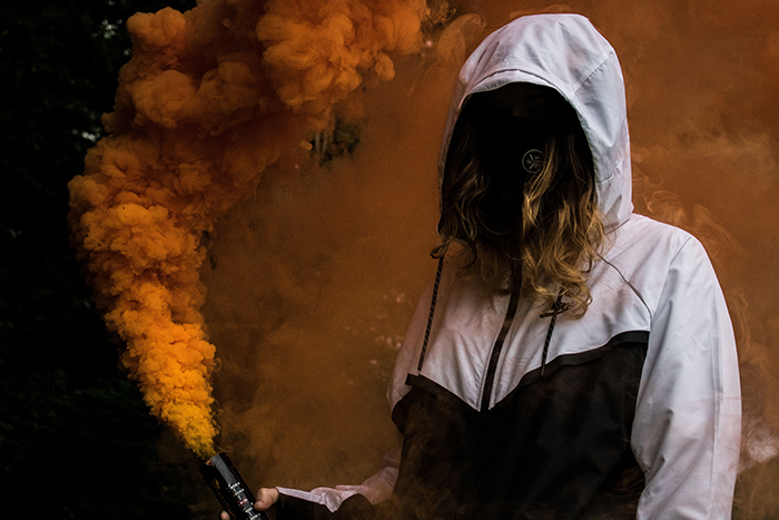 Faceless portrait of a woman holding orange smoke grenades