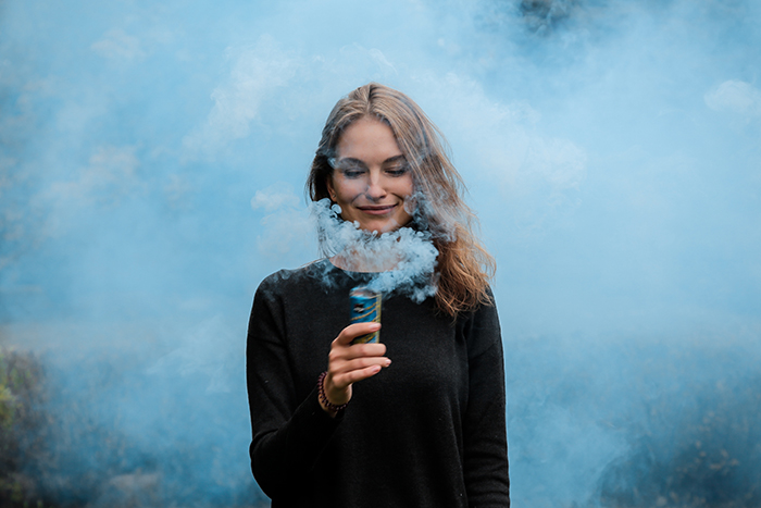 A creative portrait of a woman holding light blue smoke grenade near her face