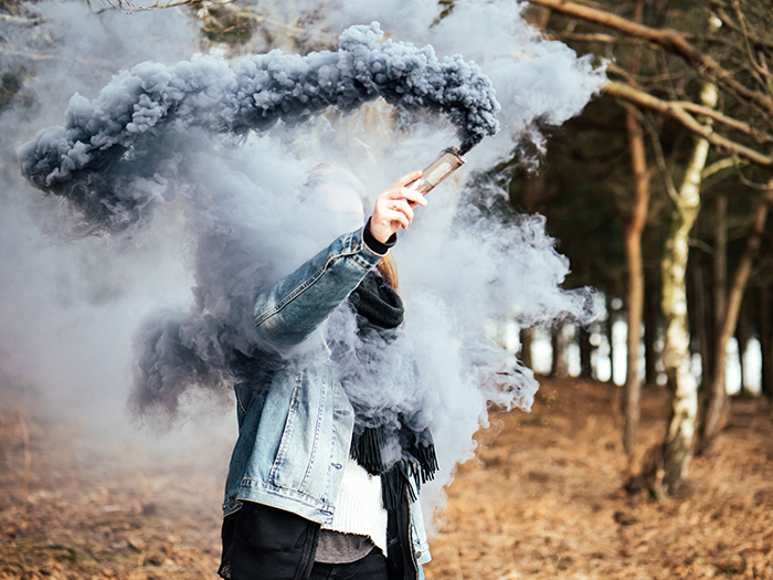 Asmoke bomb photography portrait of a woman holding blue smoke grenade near his face