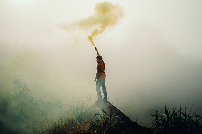 Atmospheric portrait of a man waving smoke grenades in a landscape setting