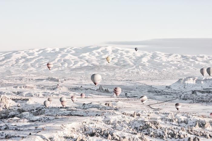 Muitos balões de ar quente voando sobre uma paisagem de neve