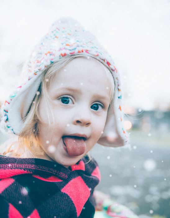 A sweet portrait of a little girl catching snowflakes in her mouth
