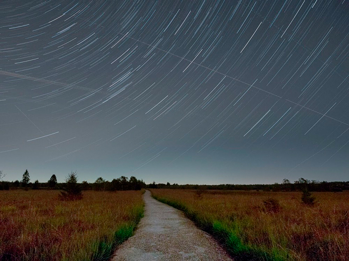 Summer star trails over a quiet countryside road