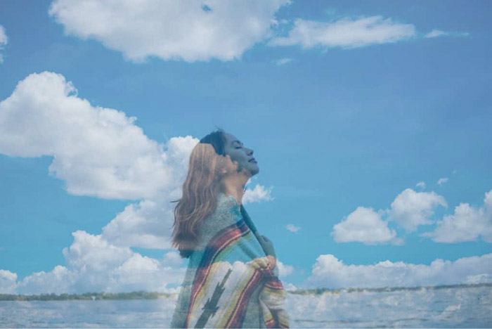 Dreamy photo of a girl superimposed with an image of fluffy clouds