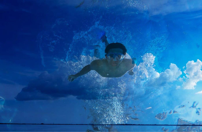 A man swimming superimposed with a photo of clouds - how to use superimpose