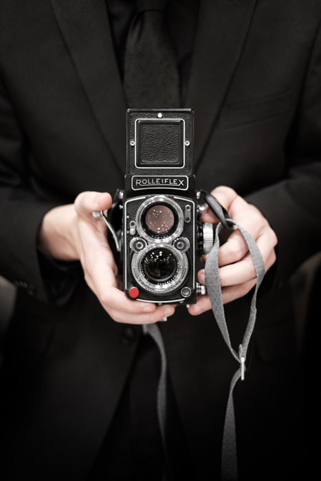 A person holding a Rolleiflex film camera - viewfinder info