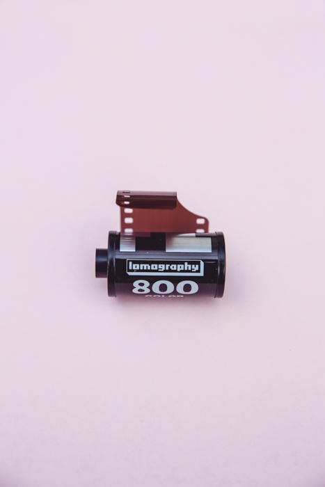 A ROLL OF LOMOGRAPHY FILM AGAINST PINK BACKGROUND