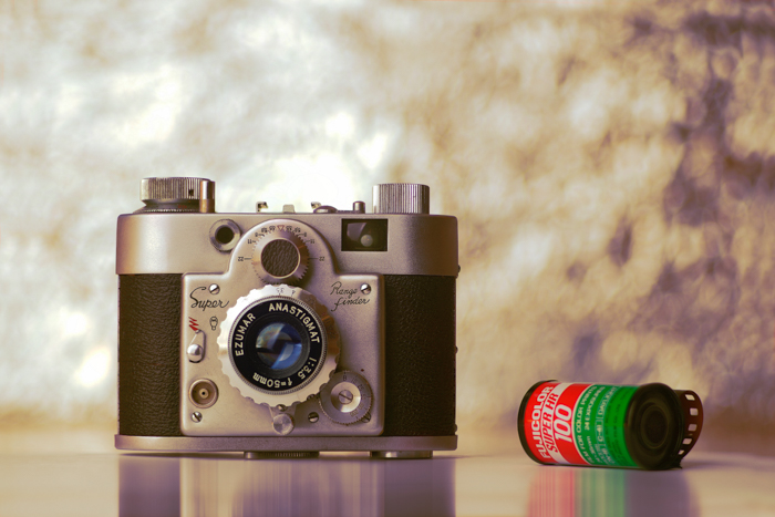 An old camera beside a roll of film - where to buy film