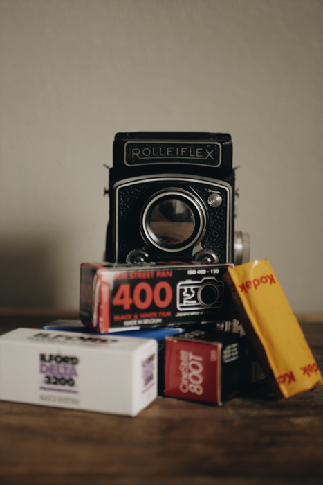 A Rolleiflex film camera propped on different film rolls - where to buy film