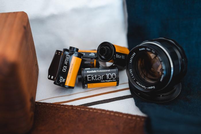 Rolls of kodak film beside a camera lens - where to buy film for old cameras