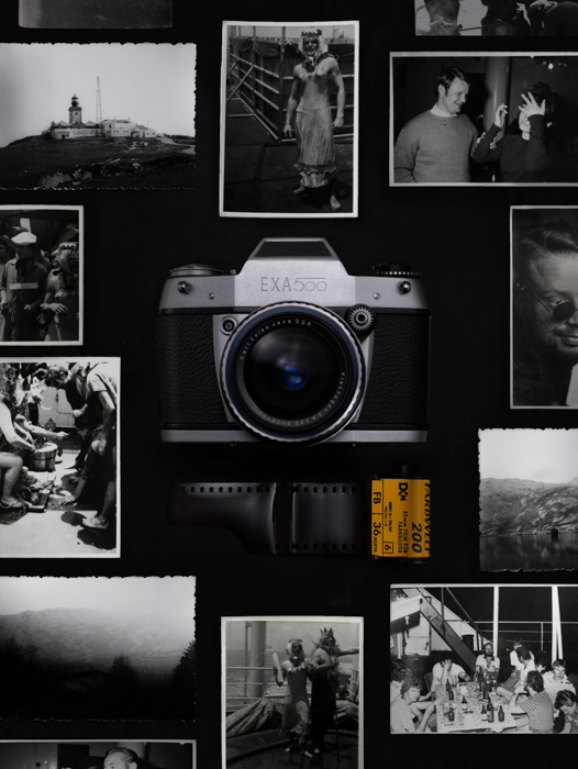 An artistic shot of an old film camera arranged among black and white photos and a roll of film