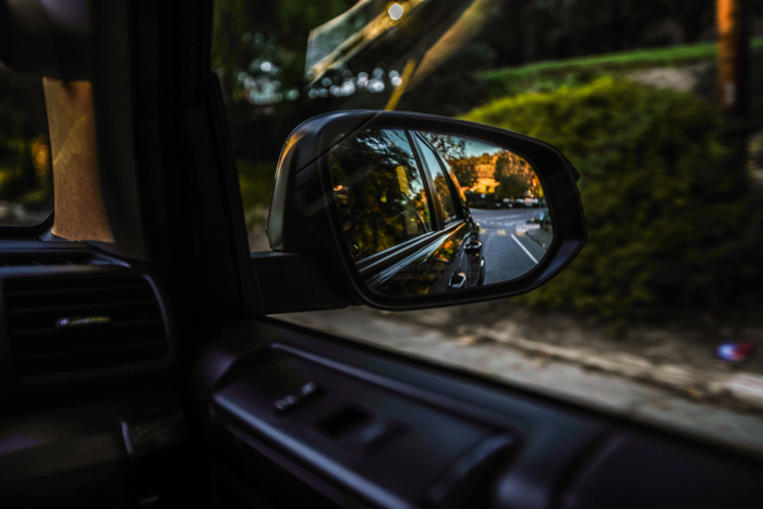 A moving car reflected in its own side mirror